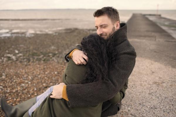 happy couple in winter coats hugging