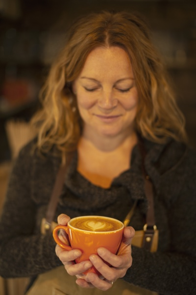 happy female barista holding cappuccino with