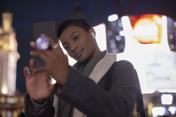 young woman taking selfie below neon
