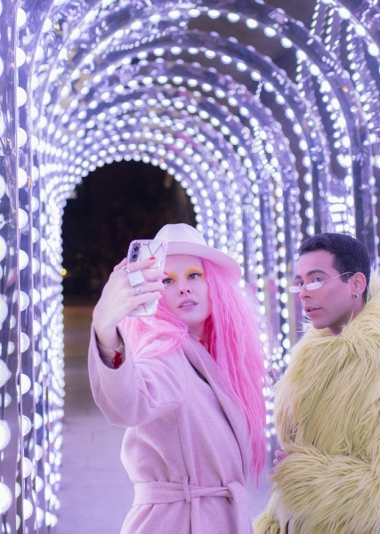 stylish couple taking selfie under arch