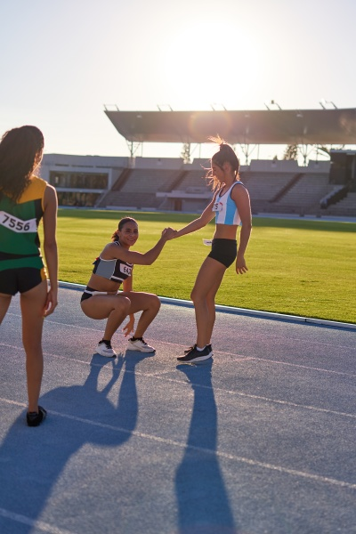 female track and field athlete helping