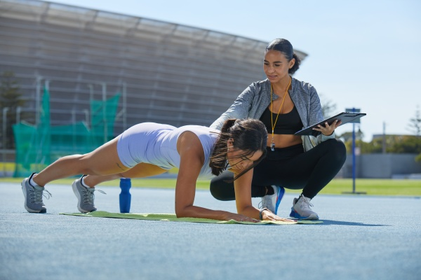 trainer helping female track and field