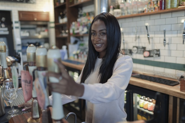 portrait happy young female bartender behind