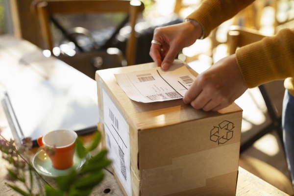 business owner placing shipping label on
