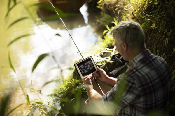 man with digital tablet fly fishing
