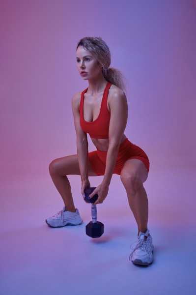 sexy female athlete poses with dumbbell