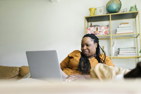 woman sitting on sofa and working