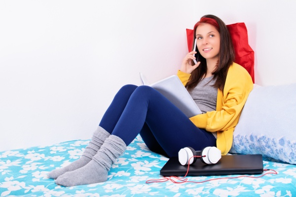 young girl sitting on her bed