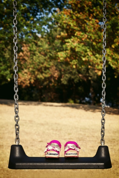 pink sandals child on swing in