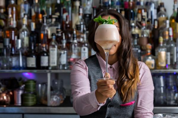 unrecognizable female mixologist showing cocktail