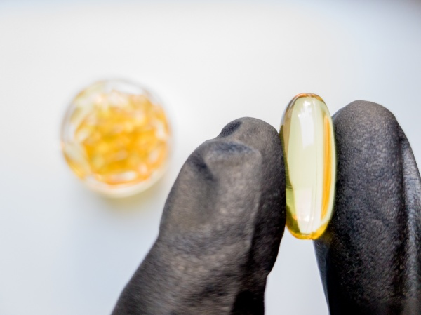 fish oil capsules in hand in