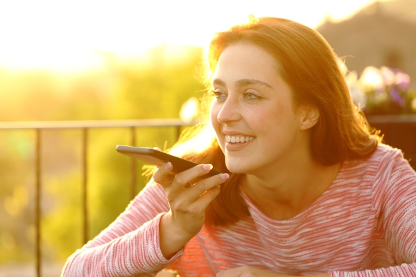 happy female using voice recognition on