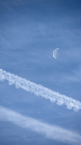 airplane contrails and waning moon against