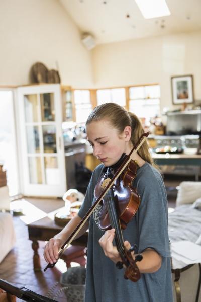 teenage girl playing her violin at