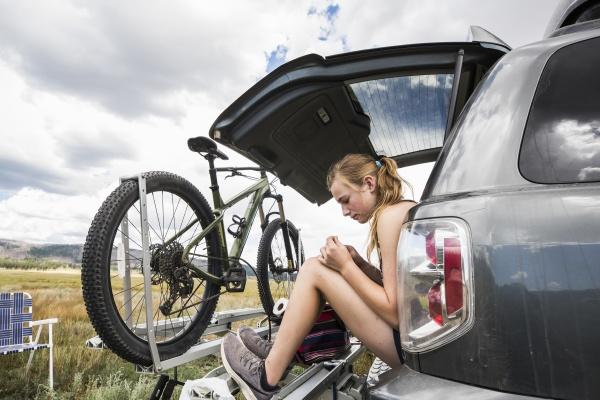 teenage girl sitting on the tailgate