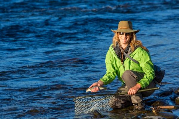 fly fisherwoman landing trout with net