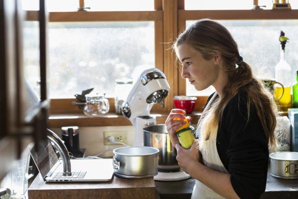 teenage girl in a kitchen following