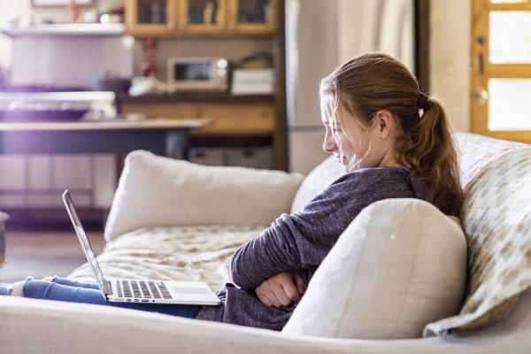 teenage girl looking at laptop on