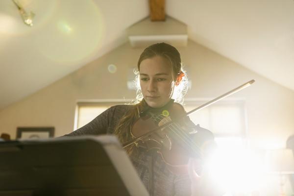teenage girl playing her violin in