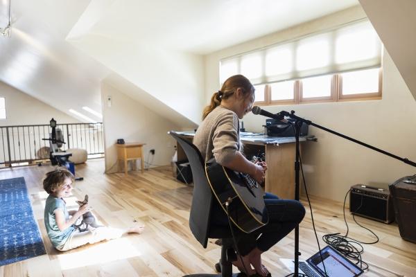 teenage girl playing her guitar and