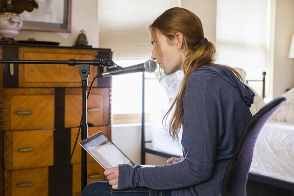 teenage girl singing into a microphone