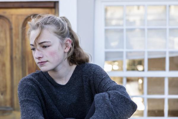 a teenage girl sitting outside alone