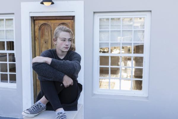 teenage girl sitting cross legged on
