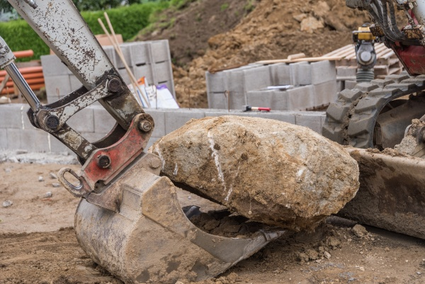 excavator with stone on excavator bucket