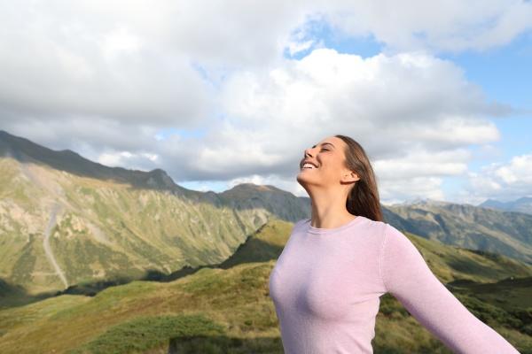 happy woman breathing fresh air alone