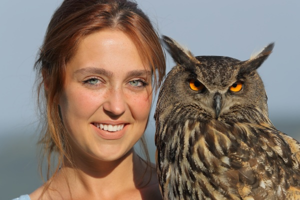 happy woman holding royal owl looking
