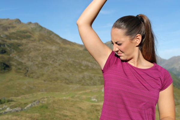 sportswoman smelling stinky armpit in nature