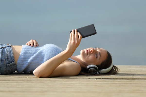 woman lying on pier listening to