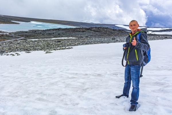 young hiker photographer at galdhopiggen jotunheimen