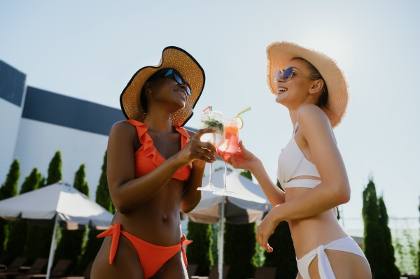 two sexy girlfriends drink coctails at