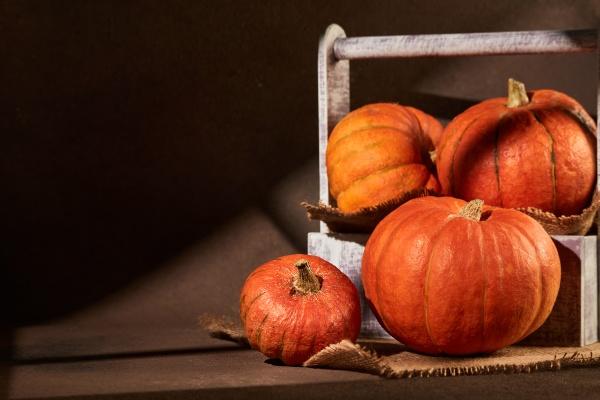 ripe orange pumpkins in wooden box