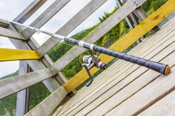 fishing rod on wooden pier by