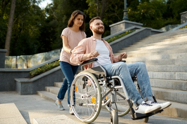 couple with wheelchair goes up the