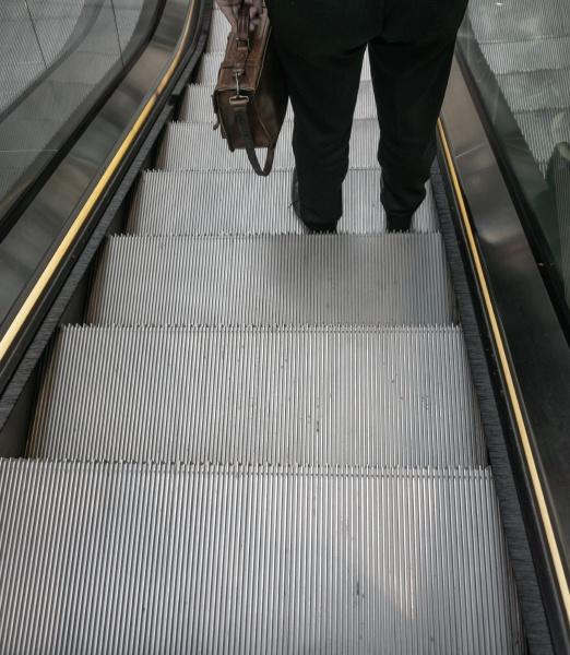 man with briefcase on escalator