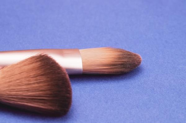 makeup brushes on blue background