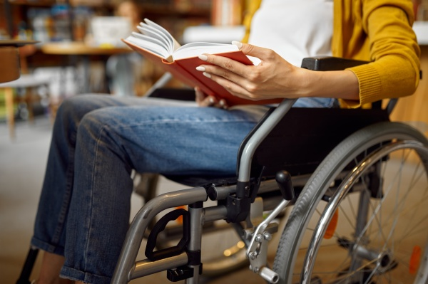 disabled student in wheelchair reading a
