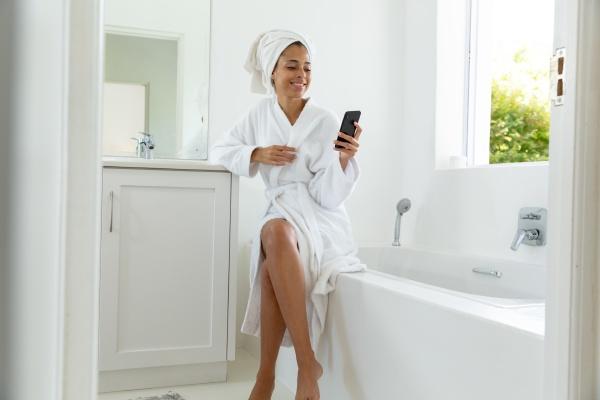 mixed race woman wearing bathrobe sitting