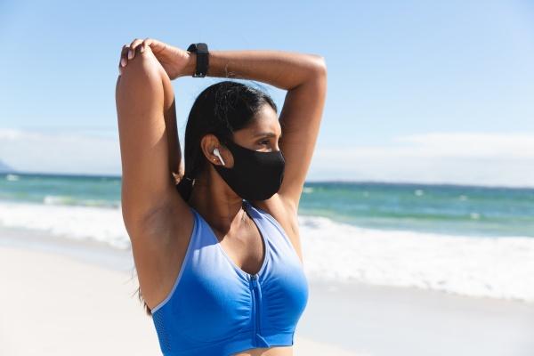 mixed race woman exercising on beach