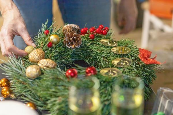 woman completes a handmade advent wreath