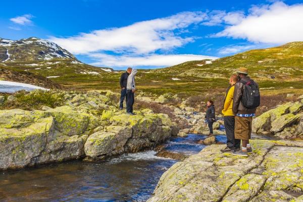 people hikers cross river of vavatn