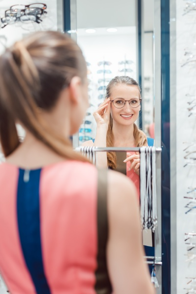 young woman trying fashionable glasses in