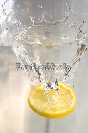 slice of lemon falling in glass