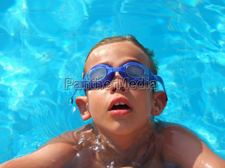 child with goggles in the pool