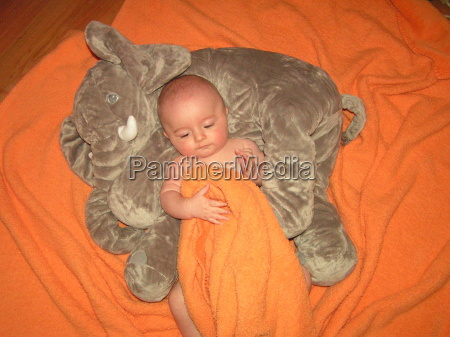 baby snuggles with elephant
