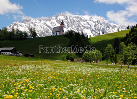 mountain meadow with chapel and mountains
