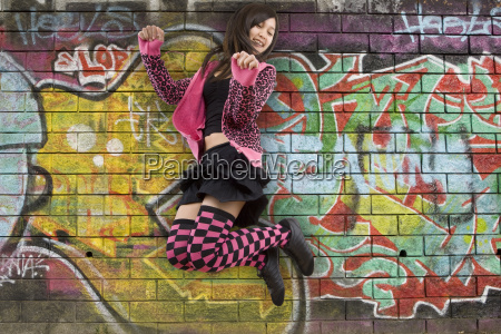 teenager jumping for a graffitywand